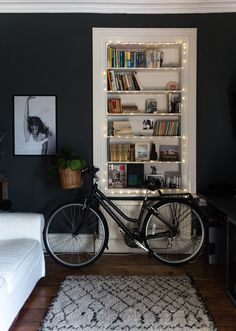 The study has a glamorous edge with its dark walls, string lights, and the unusual accessory of a bicycle.