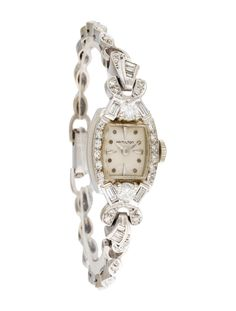 Ladies' 14K white gold 17mm x 14mm Hamilton Vintage watch with manual wind movement, diamond bezel, flat dial, index hour markers, dauphine hands, round and baguette diamonds at lugs, marquise shaped diamond link bracelet with foldover clasp closure featuring bracelet catch chain with spring ring closure.
