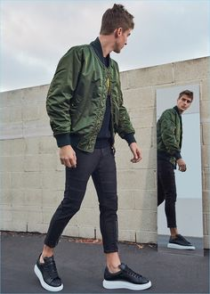 Tapping into the military trend, Samuel Roberts sports a Burberry bomber jacket with a Loewe elephant sweater, Neil Barrett biker jeans, and Alexander McQueen leather platform sneakers.