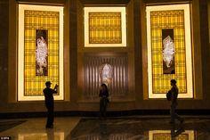 Visitors take photographs inside Macau's towering $4.5 billion Studio City casino and resort
