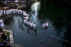 Baptism in the Jordan River as it flows out of the Sea of Galilee.