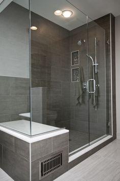 Contemporary frameless shower door, hand shower, large format tile.