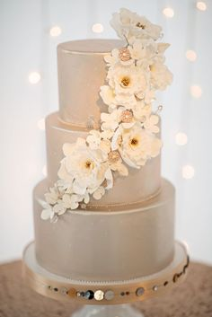 Gold wedding cake with cascading white floral decor | Photo by Kristen Weaver
