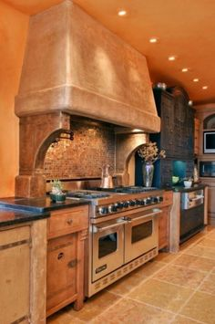 The joy is in the details of this eclectic kitchen - hand-forged hardware and hinges feel southwestern; tile backsplash and weathered range hood give a warm adobe feel; stainless elements add a contemporary punch. #VikingProfessional