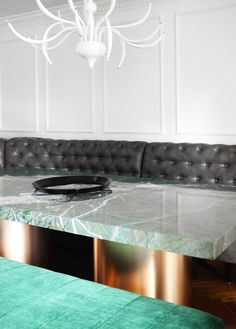 Green marble table and long, black leather tufted booth for sitting