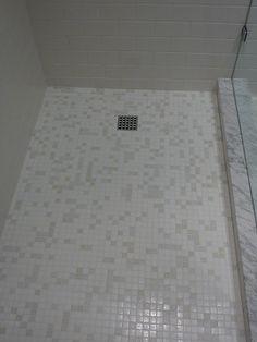 1x1 Hakatai glass tile shower floor in a 3x6 white subway shower in St. Pete, FL.