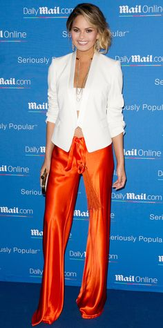 At a yacht party in Cannes, Chrissy Teigen gave her relaxed orange satin drawstring pants a sophisticated spin with a smart white blazer and a white bandeau underneath, glamming it up even further with statement earrings, a choker-chain necklace, and a white minaudiere.