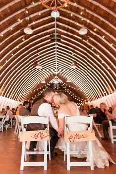 Epic Reception Kiss by Bride and Groom at Sweetheart Table in High Ceiling, Exposed Rafters Barn. A Rustic Brandy Hill Farm Wedding in Culpeper, Virginia featuring accents of cranberry and gold! Photos by Katelyn James Photography