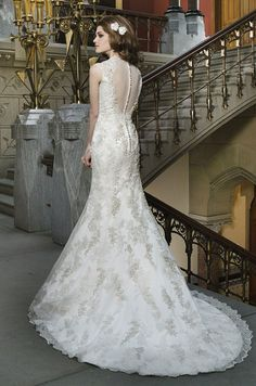 Beaded metallic venice lace appliques layered over embroidered lace to create a trumpet silhouette with a Queen Anne neckline. Justin Alexander, 2014