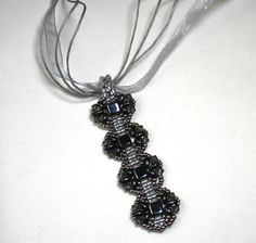 Gray+is+the+new+fashion+color+this+year+and+I+have+designed+this+long+pendant+with+five+shades+of+gray.+I+used+metallic+nickle+color+gray+small+glass+beads,+square+Hematite+color+glass+beads,+medium+gray+crystals,+dark+smoke+gray+oval+beads,+and+light+gray+for+connecting+the+segments.  This+pen...