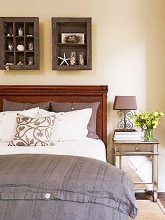 Mix of Styles A rich wood headboard gives this bedroom a slightly formal feel, while simple linen bedding and charming shadow boxes are more light-hearted. Creamy latte-color walls and the dark wood tones warm up crisp white and cloudy gray, creating a dynamic neutral color palette. A mirrored nightstand adds a touch of glamour and sparkle to complete the space.