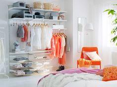 Ljust sovrum med öppen förvaring bestående av hyllplan, trådbackar och klädstänger, allt i vitt.
