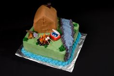 A themed cake of a campsite with a covered tent and campfire next to a river.