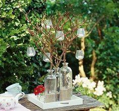 Kerzenleuchter aus der Natur. Den Kandelaber kann man ganz leicht selber machen. Ideal sind alte Glasflaschen. Mit Sand füllen für mehr Standfestigkeit. Dann kommen Zweige hinein, am besten mit schönen Verästelungen. Kleine Teelichter mit Drahtbügeln in die Zweige hängen und anzünden, sobald es dämmrig wird.