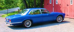"""The '87 Jaguar XJ """"restomod"""" after paint.  Notice the door handles...no?  There aren't any...the doors open with the push of a button on the key fob.   Chevy 350 conversion with real Dayton wire wheels.  Sunroof and A/C.  Fun to drive too!"""