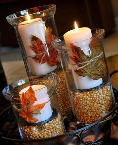 Thanksgiving or Autumn table decoration. Very easy- cheap popcorn kernels, dollar store candles, leaves from the dollar store, in glass holders