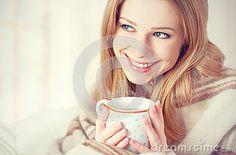 Glückliche junge Frau ist unter einer Decke und einem Tasse Kaffee auf Wintermorgen zu Hause