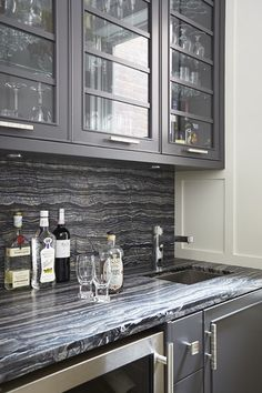 Contemporary bar and butler's pantry featuring charcoal cabinetry and dramatic countertop designed by Douglas Design Studio.