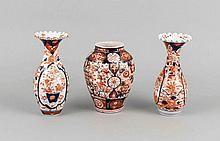 Drei Vasen, Japan, 19./20. Jh., Imari, floraler Dekor in Unterglasurblau und Überglasurrot, ziervergoldet, bauchige Vase, H. 16 cm, 2 Vasen mit gewelltem Lippenrand, 1 best., H. 18 cm