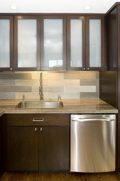 wow, love this kitchen, the stain color, frosted glass, and that backsplash!!