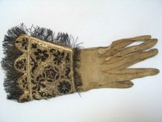 Glove 1580-1600.  Dates from the reign of Queen Elizabeth 1.  Gloves of 'cordwain' (white tawed goatskin), the flesh side outward and stained light brown. The cuffs covered with fawn silk embroidered with silver-gilt wire and seed pearls. The slits were made to display jeweled rings