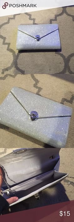 Silver Metallic Clutch Silver Metallic Clutch used once, as detachable silver chain strap,, has 2 seperate compartments and a zipper compartment!! Nice amount of space for a wedding or dressy affair!! Measurements are 10x6 inches Bags Clutches & Wristlets