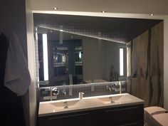 Custom shape backlit mirror with LED lighting integrated in mirror.
