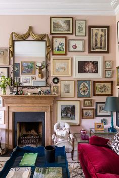 """Etro's scrumptious raspberry-red cotton velvet """"Palinuro"""" from Pierre Frey covers the sofa by the fireplace. The wood mantle was found at Petworth Antiques Market. This room looks like it decorated itself over time with family furniture and art."""