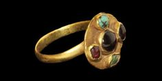Circa 5th century AD. A gold finger ring with plain D-section hoop and discoid pad on underside; the bezel a pedestal with discoid face bearing two turquoise and three garnet cabochon stones in a quincunx pattern. Gold, garnet and turquoise, 5.76 grams, 26 mm overall (approximate size British N 1/2, USA 6 3/4, Europe 14.35, Japan 14).