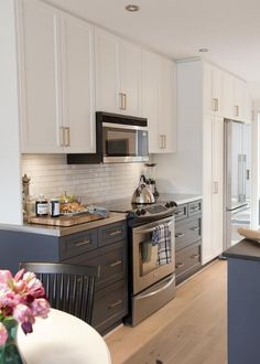 Contrasting kitchen cabinets. island and sink lowers same colour.  Appliance wall and sink uppers same colour