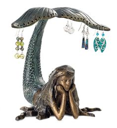 A mermaid lazes in the water, idly swishing her tail while dreaming of gems and jewels. Hang your earrings on the mermaid's tail, let her wear a ring as a crown - she'll be delighted. Metal jewelry holder has antiqued-bronze and verdigris finish. - Mermaid Earring Holder