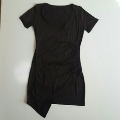 """Black Cinched Waist Asymmetrical Hemline Dress This lovely black dress mini tight form fitting dresa has a v neck line and short sleeves, the material is cinched in at the left side and the bottom the hemline is not straight, one corner comes down in front over your left thigh. This dress is made of stretchy  polyester material and is a medium. Measurements are bust is 34"""" waist is 29"""" and hips is 34"""" this is brand new and unused. Other great accessories in my closet. Classic and beautiful…"""