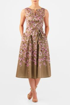 A split neck tops our cherry blossom with bird print polydupioni dress designed with an angled pleat bodice and sash tied waist atop a full flared skirt.
