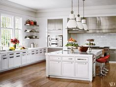 At the Greenwich, Connecticut, estate of former Sony executive Tommy Mottola and his wife, pop singer and actress Thalia, interiors firm Katch I.D. equipped the kitchen with a trio of circa-1930 Czech lights from Ann-Morris, cabinetry