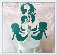 """Mermaid Birthday Party Cake Topper. We've taken the concept of a Mermaid birthday party and elevated a Mermaid cake topper with high quality glitter cardstock. This Mermaid decoration is further distinguished with the use of real lace ribbon making it a three-dimensional embellishment that is truly fit for the little mermaid. Great as a centerpiece pick for your centerpieces. If you are going to use as a centerpiece pick please let me know and I will attach to a 12"""" long wooden pole...."""