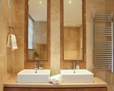 photo of beige brown orange bathroom and furniture towel holder The long mirror on darker coloured tiles certainly looks very luxury