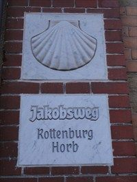 There's a marker at a building in the 'Sprollstraße' in Rottenurg, Germany, Baden-Württemberg. The marker indicates that this is the part 'Rottenburg - Horb' of the Way of St. James.