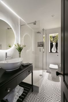 """""""The bathroom is quite small with limited light so here we used lots of mirrors and glass to create a feeling of space and openness. I love the halo effect on the back-lit mirror over the bespoke vanity unit; it's so soft and warming."""" The geometric floor tiles in the bathroom are from Marrakechdesign."""