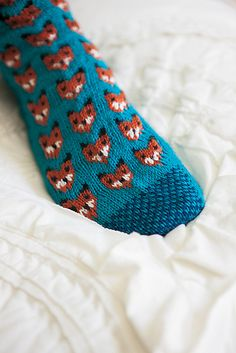 Worked from the toe up, this is a pair of socks that will not be easily forgotten. Adorable knitted foxes and a two color sole make this pattern whimsical, wonderful, and sly as a fox! Every moment of knitting them will be an experience you won't forget.