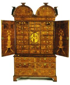 Made in Yorkshire by John Byfield in 1700 The cabinet was made in about 1700 to commemorate the marriage of Margaret Trotter to George Lawson. The couple's monograms can be seen on the outer doors, while the arms of the two families can be found on the door of the inner cupboard.  The cabinet passed to Margaret's sister Mrs Catherine Bower who in turn left it to her son Henry in her will, dated 21 April 1742: