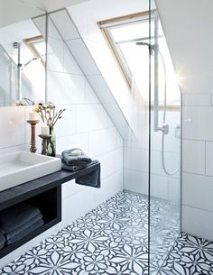 Trend Watch: Add some beautiful tiles to your bathroom to make it more individual. We love the flower design in this bright bathroom. It fits perfectly to the black and white sink.  Click to find more inspiration for your bathroom.