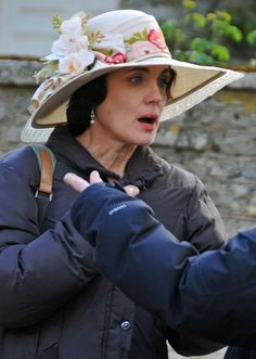 Elizabeth Mcgovern (Cora)  Lovely, Lilting, wide brimmed white & flowered be-ribboned hat.