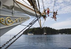 Olivia Trankina of Marietta, Ga., and Liz Archibald of Clarks Summit, Penn., leap from the bowsprit of the schooner Mary Day in Bucks Harbor in South Brooksville, Maine. (AP Photo/Robert F. Bukaty)