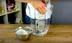 Sie stellt eine kleine Vase in eine größere und legt Kieselsteine hinein. Der Grund dafür ist der Hammer!