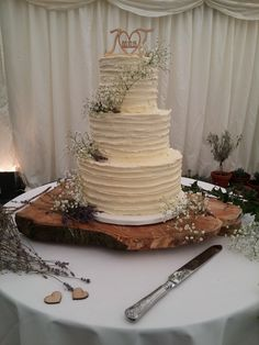 Buttercream finished wedding cake with fresh lavender and gypsophila on rustic tree stump