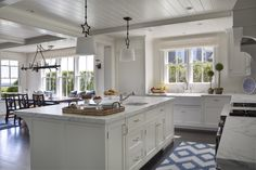 High gloss wood panels and star motif pendants over a marble kitchen island white shiplap coffered ceiling