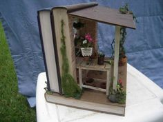 """Shannon Moore's """"Potting shed,"""" sideview, made from three books. More of Moore's book art is at the link, """"Books in the hands of Shannon Moore"""" at Book Patrol. Book Crafts, Diy And Crafts, Paper Crafts, Miniature Rooms, Miniature Fairy Gardens, Altered Books, Altered Art, Book Sculpture, Fairy Doors"""