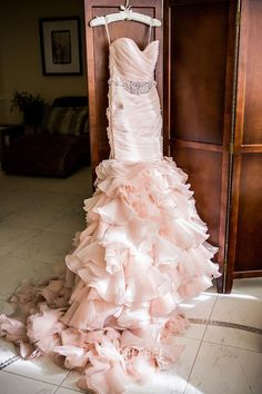 Blush pink colored wedding dress, strapless beaded ruched bodice, layered ruffled skirt, lace up back, mermaid organza flange skirt with sweep train.