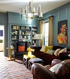 love the mix of leather, wood and velvet with the blue walls in this library
