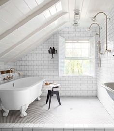 """The now-luxurious area is kitted out with a dual shower and a claw-foot tub from Victoria + Albert, all finished with fittings from Habitat, a local hardware store. The hanging basket, once used by miners, holds toiletries. The Shaffers widened the window opening, and tilted the floor at a slight slant for drainage. """"It was worth every penny!"""" says Leanne."""